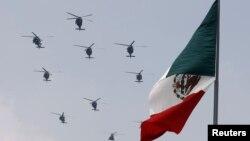 Helicópteros de la Fuerza Aérea de México vuelan en formación durante un desfile militar el Día de la Independencia que celebra en la plaza del Zócalo de la Ciudad de México.