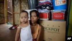 Cô Emily Sagalis và bé Bea Joy, những người sống sót sau trận bão Haiyan, trong ngôi nhà của họ ở Tacloban, 5/11/2014.