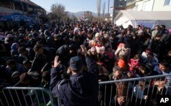 Serbian police officer attempt to organize migrants queuing to get registered at a refugee center in the southern Serbian town of Presevo, Nov. 16, 2015.