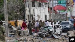 Lực lượng an ninh bảo vệ hiện trường bên cạnh chiếc xe đã bị phá hủy sau vụ đánh bom liều chết ở thủ đô Mogadishu, Somalia, hôm 26/72015.