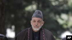 Afghan President Hamid Karzai arrives for a press conference, September 22, 2011, honoring former Afghan President Burhanuddin Rabbani who was killed two days ago in Kabul.