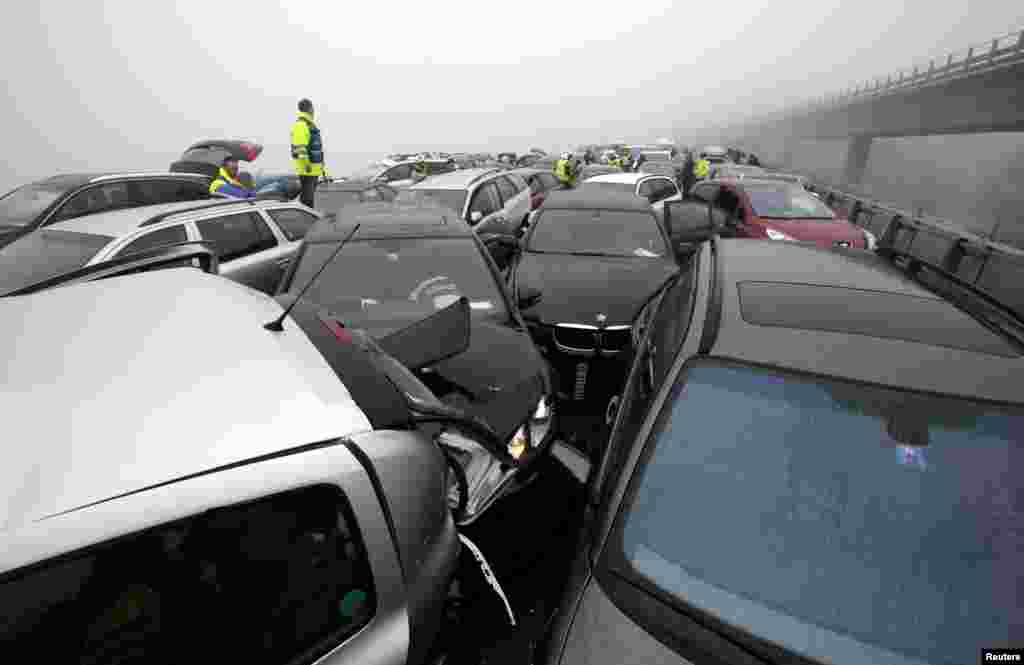 A first aid worker stands on a car at the site of a pileup on the A9 motorway near Chexbres, Switzerland. About 50 cars were involved in the pileup but no one was seriously injured, according to local media.