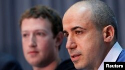 Russian entrepreneur and venture capitalist Yuri Milner (R) speaks while Facebook CEO Mark Zuckerberg looks on at the Life Sciences Breakthrough Prize announcement in San Francisco, California, Feb. 20, 2013.