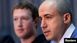 FILE - Russian entrepreneur and venture capitalist Yuri Milner (R) speaks while Facebook CEO Mark Zuckerberg looks on at the Life Sciences Breakthrough Prize announcement in San Francisco, California, Feb. 20, 2013.