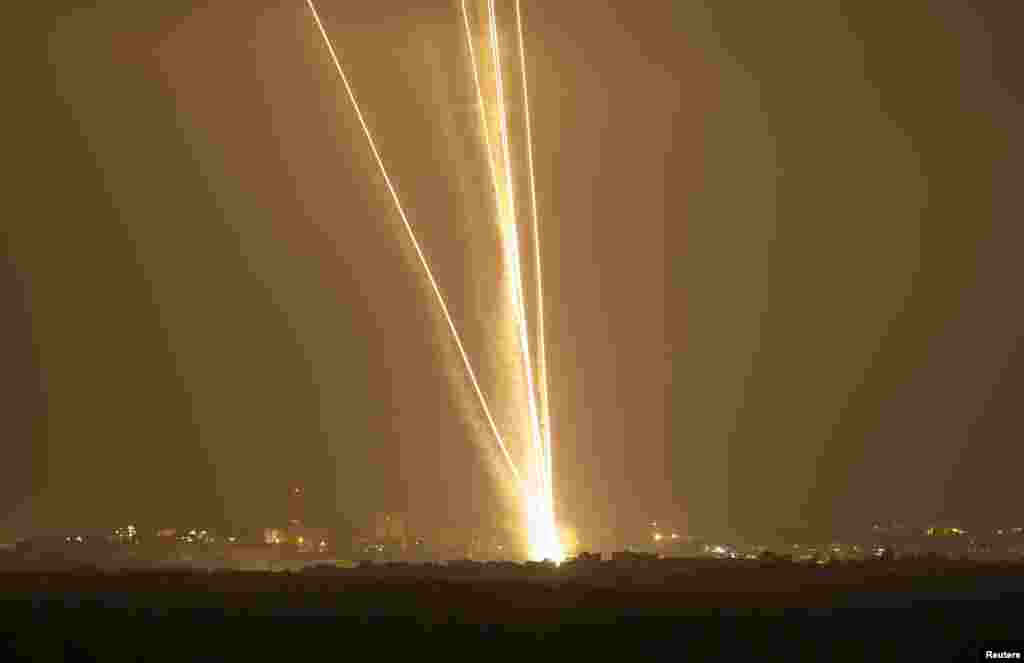 Light streaks and smoke trails are seen as rockets are launched from Gaza towards Israel, July 23, 2014.