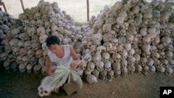 FILE - A man cleans a skull near a mass grave at the Chaung Ek torture camp run by the Khmer Rouge in this undated photo. The last surviving leaders of the Khmer Rouge regime were convicted of genocide, crimes against humanity and war crimes Nov. 16 by an international tribunal.