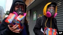 Warga mengenakan masker penutup wajah sambil membawa paket berisi masker sekali pakai di Hong Kong, 5 Februari 2020.