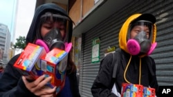 Citizens wearing full mask respirators carry packets of disposable face masks in Hong Kong, Wednesday, Feb. 5, 2020. (AP Photo/Vincent Yu)