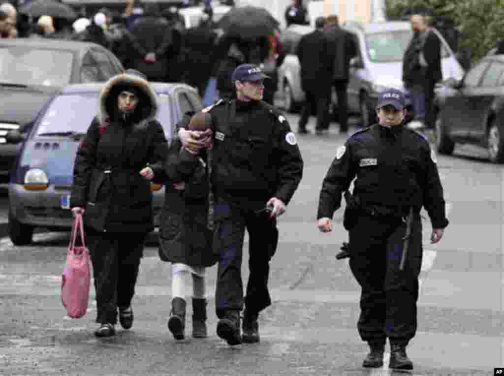 A student, second from left, is flanked by an unidentified woman and police officers as they leave a Jewish school after a gunman opened fire in Toulouse, southwestern France, Monday, March 19, 2012. A father and his two sons were among four people who di