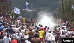FILE - A still image taken from a video shot on Oct. 1, 2017, shows protesters waving Ambazonian flags as they move forward towards barricades and police amid tear gas in the English-speaking city of Bamenda, Cameroon.