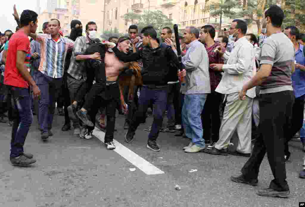 Egyptian security forces and civilians detain a supporter of ousted Egyptian President Mohamed Morsi near Ramsis Square, Cairo, Oct. 6, 2013.