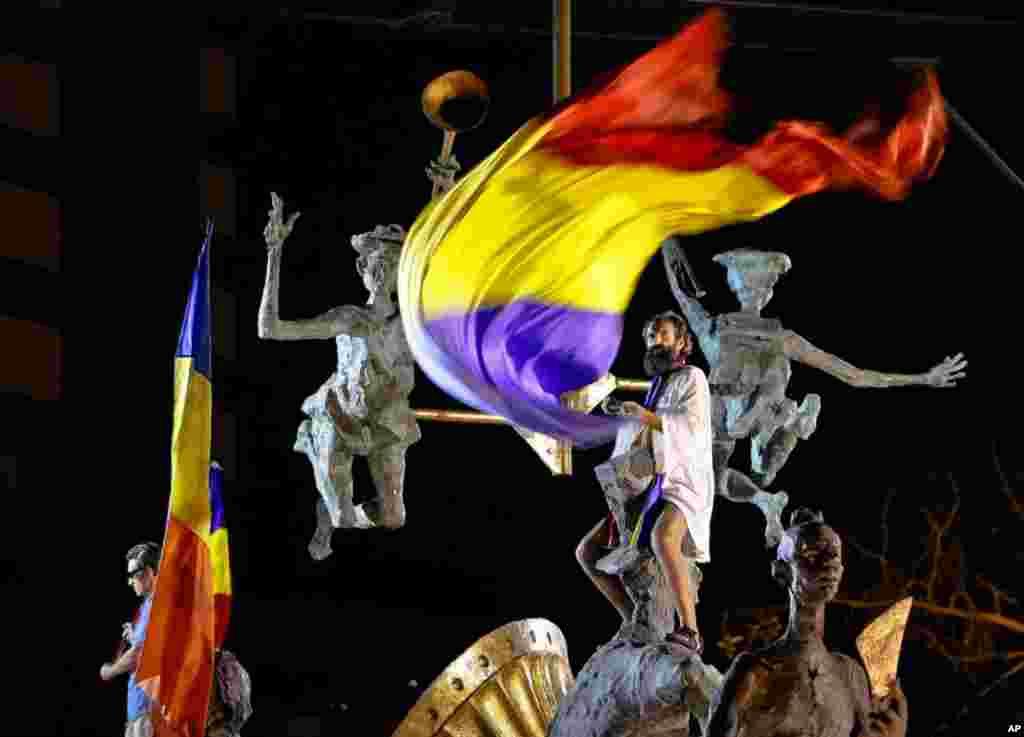 مردی پرچم رومانی را طی اعتراضات عليه ترايان باسسکو، رييس جمهوری در دست دارد.(AP)