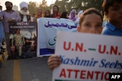 Pakistani Kashmiris carry placards to show their solidarity with Indian Kashmiri Muslims during an anti-Indian protest in Islamabad on Sept. 26, 2016.