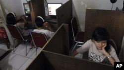 FILE - Indonesian youths browse at an internet cafe in Jakarta, Indonesia. (AP Photo/Tatan Syuflana)