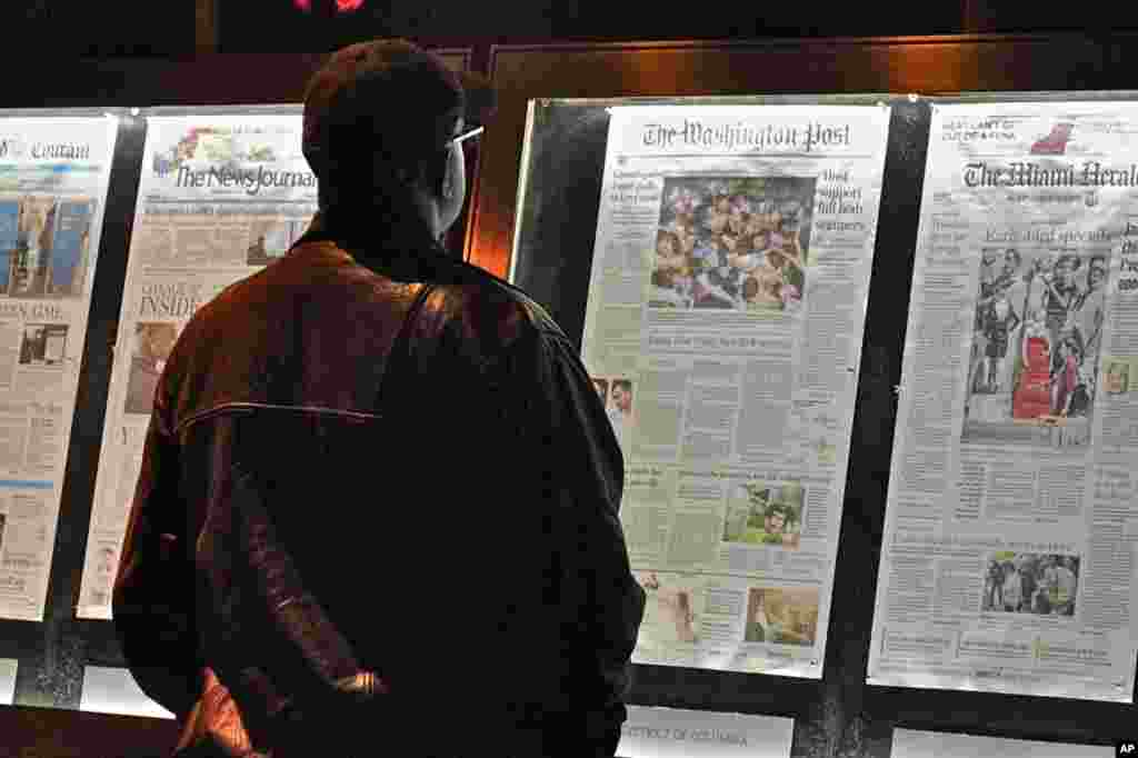 A passersby examine the main photo of the stampede in Cambodia on the front page of Washington Post of November 23, 2010.