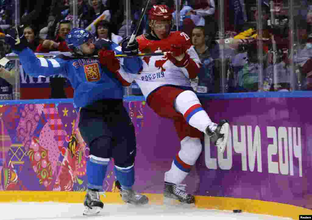 Russia's Alexander Syomin (right) and Finland's Sami Vatanen battle along the boards during the first period of their men's quarter-final ice hockey game, Sochi, Feb. 19, 2014.
