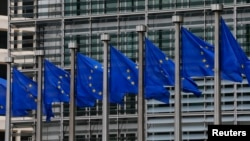 FILE - European Union flags are seen outside the European Commission headquarters in Brussels, Sept. 10, 2014.