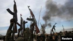 Des combattants rebelles marchent avec leurs armes en l'air dans le territoire rebelle de l'Upper Nile State, au Soudan du Sud, le 13 février 2014.
