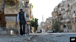 A Syrian rebel walks in Khaldiyeh neighborhood, Homs province, May 15, 2012.