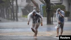 日本遭受颱風黃蜂襲擊,沖繩島兩名居民抵禦強風走上街上。