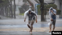 People struggle against strong wind and rain caused by approaching Typhoon Vongfong as they wallk on a street in Naha on Japan's southern island of Okinawa, in this photo taken by Kyodo, Oct. 11, 2014.