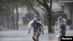 Warga di jalanan kota Naha di Okinawa, Jepang, di tengah badai Vongfong (11/10).