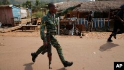 Un policier centrafricain pourchasse des pillards qui attaquent un camion en panne au PK 12, le dernier point de contrôle à la sortie de Bangui, 7 février 2014. (AP Photo / Jerome Delay)