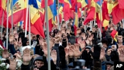 FILE - People raise their hands during an anti-government protest in Chisinau, Moldova, Jan. 24, 2016. The election of a pro-Russian president in the impoverished former Sovet republic is widely seen as a vote against the pro-Europe policies of previous Moldovan leaders.