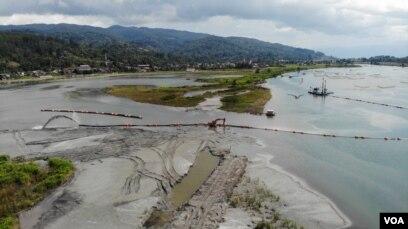 Aktifitas kapal pengeruk di Kawasan Kompo Dongi (kiri layar) seluas 35 hektar yang akan ditimbun menggunakan material hasil pengerukan dari sungai untuk dijadikan Taman Konservasi Dongi dan kawasan perlindungan burung dalam kegiatan Penataan Sungai Poso. (Foto: VOA/Yoanes Litha)
