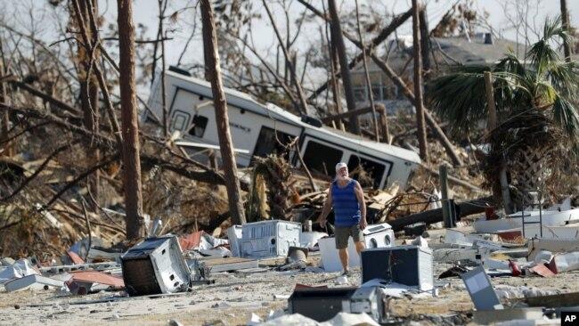 Ronnie Poole camina a través de los escombros mientras revisa la casa de un amigo después del huracán Michael en Mexico Beach, Florida, el 17 de octubre de 2018.