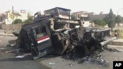 Chiếc xe bọc thép của quân đội Iraq bị đốt cháy trên đường phố của thành phố Mosul, Iraq, ngày 12/06/2014