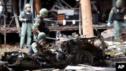 FILE - Thai bomb squad officers examine the wreckage of a car after an explosion outside a hotel in Pattani province, southern Thailand, Aug. 24, 2016.