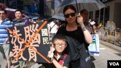 9 歲的小學生陳同學手持標語與媽媽陳太太一起參加729反洗腦大遊行