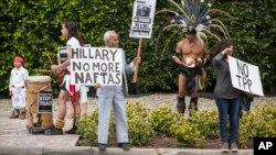FILE - Los Angeles community members wait for Hillary Clinton's motorcade as they show their opposition to the Trans-Pacific Partnership in Beverly Hills, Calif., May 7, 2015.