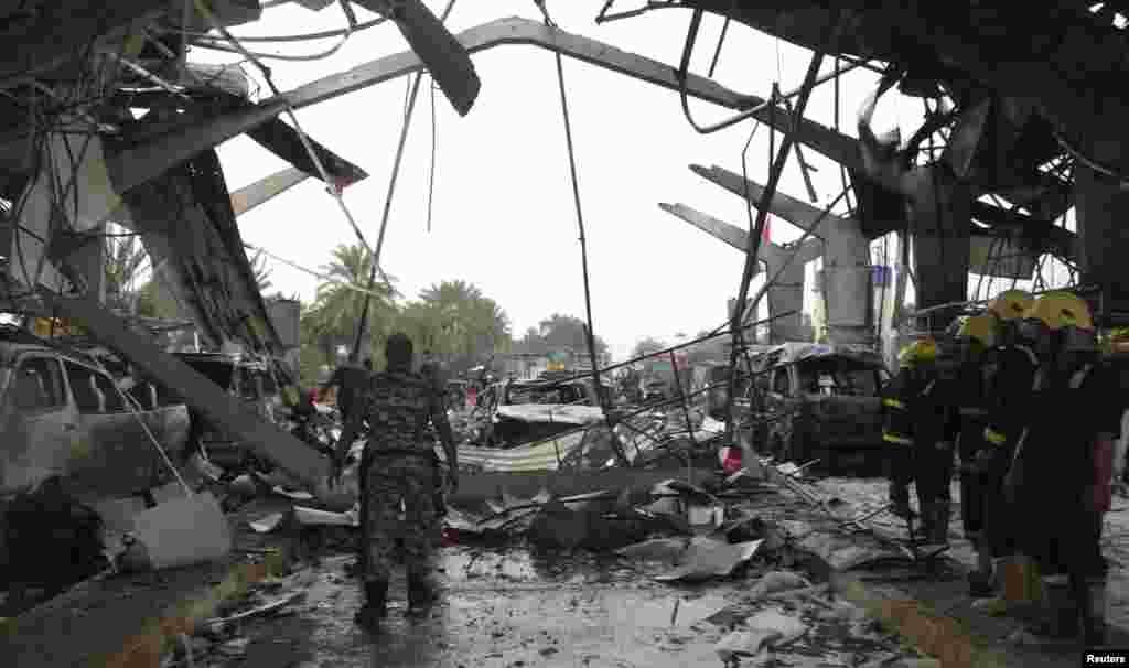 ماموران آتش نشانی و نيروهای انتظامی محل انفجار در حله (۹۰کيلومتری جنوب بغداد) را بررسی می کنند. - ۱۸ اسفندماه