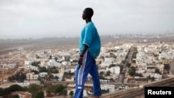 Un Dakarois regarde la ville en contrebas.