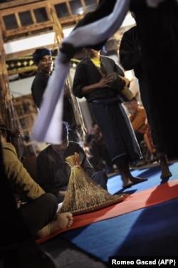 """Upacara berdoa di depan seikat padi yang baru dipanen di Istana Cigugur Pangeran Djati Kesuma, dihiasi dengan buah-buahan yang baru dipanen dalam upacara panen tahunan tradisional selama seminggu yang dikenal sebagai """"Seren Taun"""" di desa Cigugur, Barat Ja"""