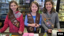 From left, Girl Scout Troop 2398 members Sara Paget, Nora Nowicki and Olivia Shea peddle cookies at a retail shop in Arlington, Va., Feb. 22, 2015. (Carol Guensburg / VOA)