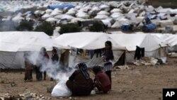 Phụ nữ Syria nhóm lửa bên cạnh lều của họ tại một trại tị nạn ở làng Atmeh, Syria, 11/12/2012