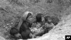 A Cambodian woman with five children apprehensively looks upwards from the shallow bunker as shells from the insurgent forces start falling in the area in the encircled capital of Phnom Penh, in March 1975.
