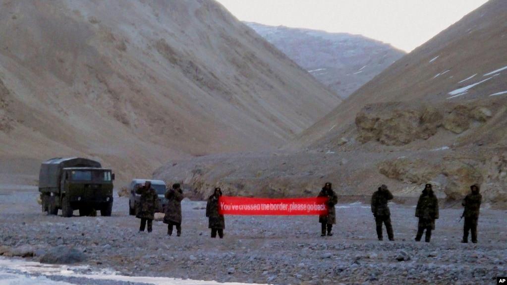 """Quân Trung Quốc cầm biểu ngữ viết """"Quí vị đã đi qua biên giới, hãy quay lại"""" ở Ladakh, Ấn Độ (ảnh tư liệu, 5/2013)"""