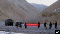 "FILE - In this May 5, 2013, file photo, Chinese troops hold a banner which reads ""You've crossed the border, please go back"" in Ladakh, India."
