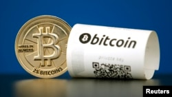 FILE - A bitcoin (virtual currency) paper wallet with QR codes and a coin are seen in an illustration picture taken at La Maison du Bitcoin in Paris, May 27, 2015.