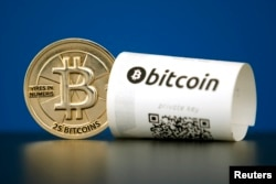 FILE - A Bitcoin (virtual currency) paper wallet with QR codes and a coin are seen in an illustration picture taken at La Maison du Bitcoin in Paris, France, May 27, 2015.