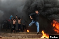 A Palestinian demonstrator runs during a protest calling for lifting the blockade on Gaza, at the Israel-Gaza border fence in Gaza, Oct. 26, 2018.