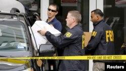 Les agents du FBI emportent des documents et autres objets lors d'une perquisition des bureaux d'Imagina à Miami, Floride, 3 décembre 2015