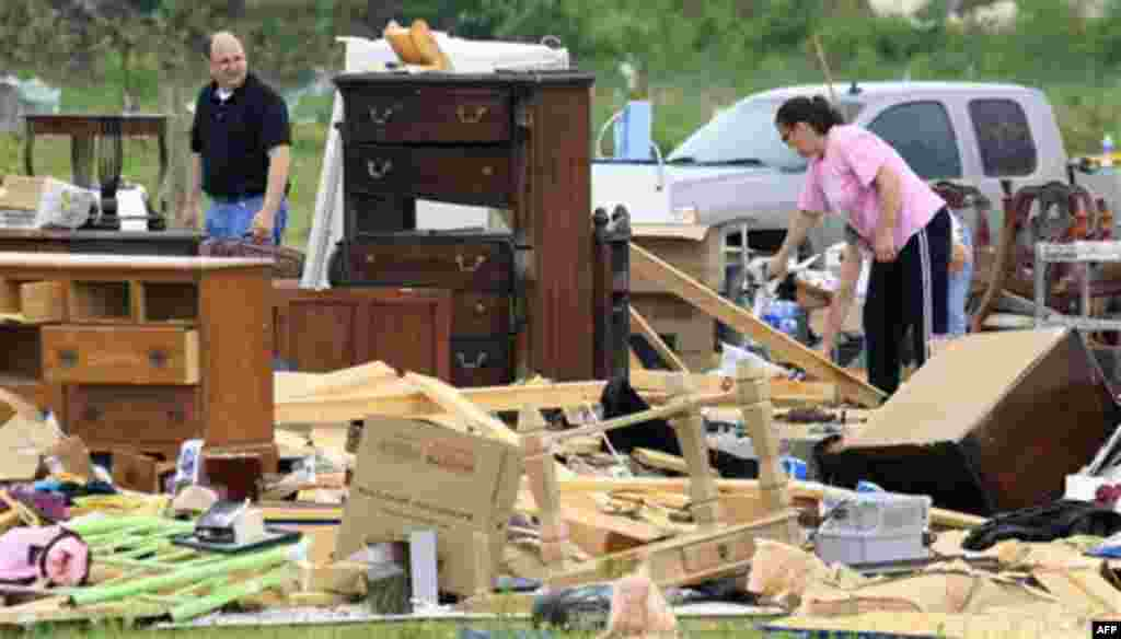 Carla Arendal, right, looks for items to save on Tuesday, April 26, 2011, after her home was destroyed by a tornado in Vilonia, Ark. Arendal and her husband were in the home during the storm but were uninjured. Helping to recover items is Arendal's minist