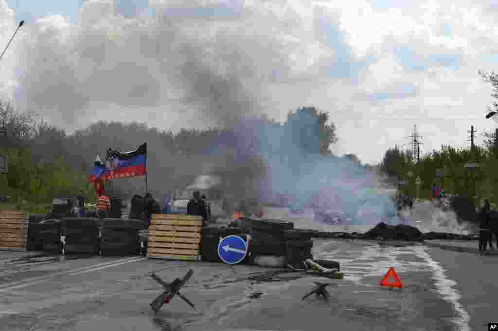 Smoke billows from burning tires at a pro-Russian checkpoint with a Donetsk republic flag following an attack by Ukrainian troops in Kramatorsk, Ukraine, May 3, 2014.