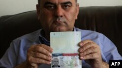 Fuad Sharef Suleman shows his US immigrant visa in Arbil, the capital of the Kurdish autonomous region in northern Iraq, Jan. 30, 2017, after returning to Iraq from Egypt, where him and his family were prevented from boarding a plane to the U.S. following President Donald Trump's decision to temporarily bar travelers from seven countries, including Iraq.
