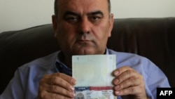 Fuad Sharef Suleman shows his US immigrant visa in Arbil, the capital of the Kurdish autonomous region in northern Iraq, on January 30, 2017 after returning to Iraq from Egypt, where him and his family were prevented from boarding a plane to the U.S. foll